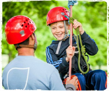 Boy and instructor tree climbing