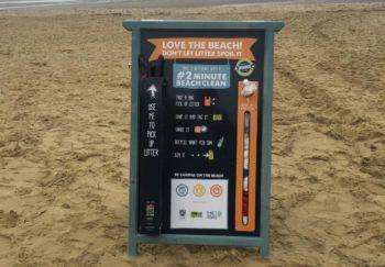 A 2 minute beach clean board standing on a sandy beach